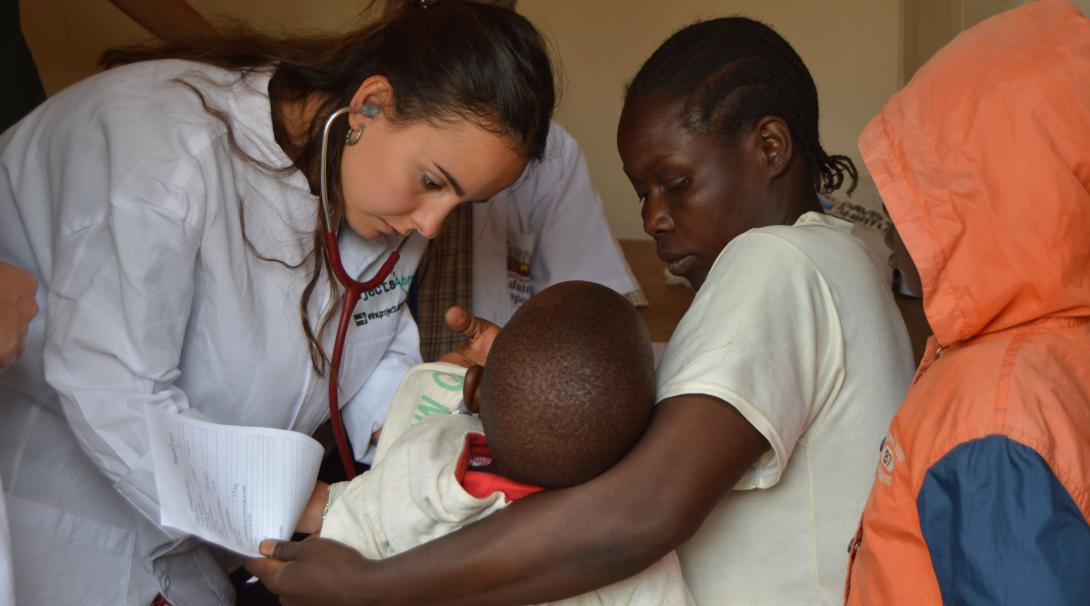 A Tanzanian child is examined by a student on a medical gap year program.
